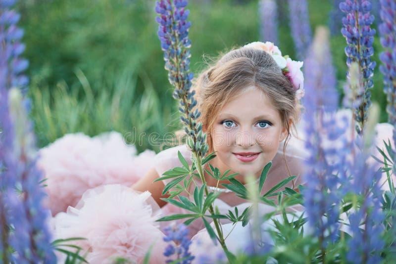 Härlig flicka i den rosa klänningen som rymmer en lupine på solnedgången på fältet Begreppet av naturen och romans lycklig barndo royaltyfri fotografi
