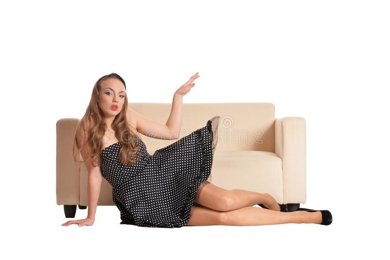 Härlig flicka i den svarta klänningen som poserar nära soffan arkivfoton