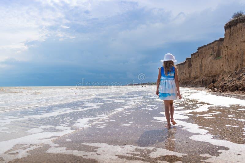 Härlig flicka i den vita hatten och färgrik klänning på kusten över bakgrund för blå himmel arkivbilder