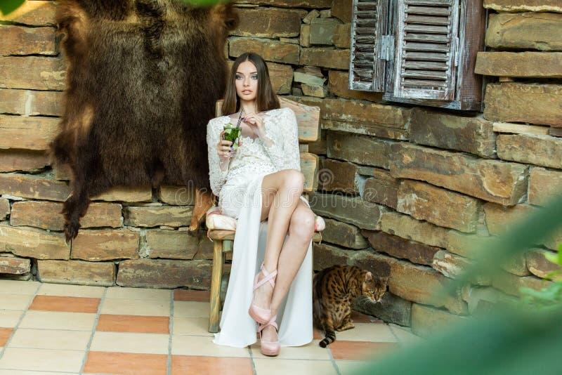 Härlig flicka i den vita klänningen som poserar med ett exponeringsglas av mojito i hennes händer arkivbild