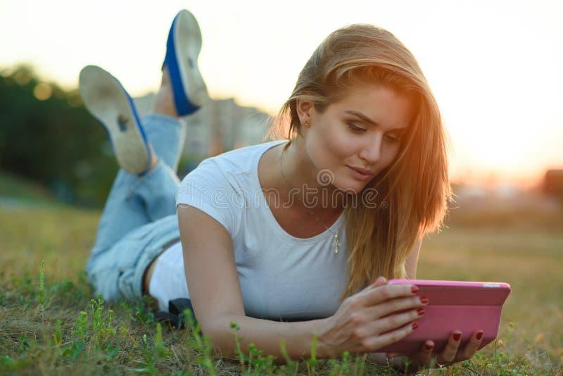 Härlig flicka i den vita T-tröja och jeans som ligger i gräset på fältet som talar till någon via hennes minnestavlaPC royaltyfri bild