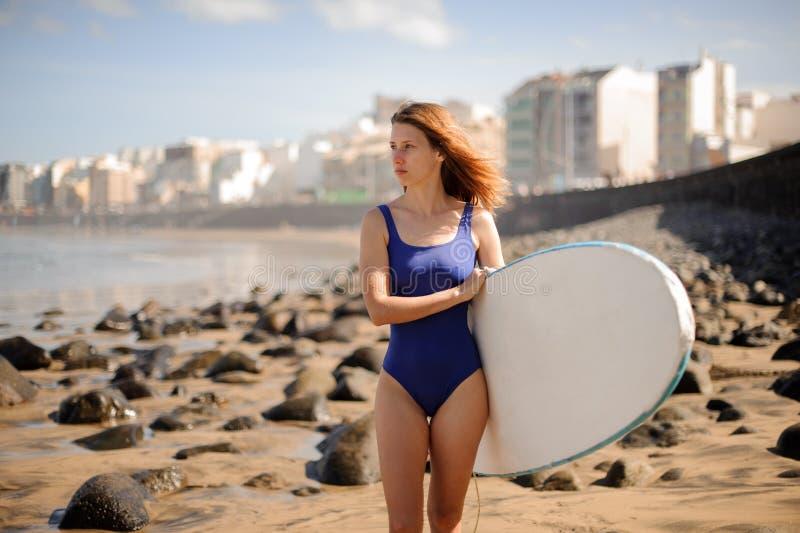 Härlig flicka i det blåa baddräktanseendet med den vita surfingbrädan royaltyfri fotografi