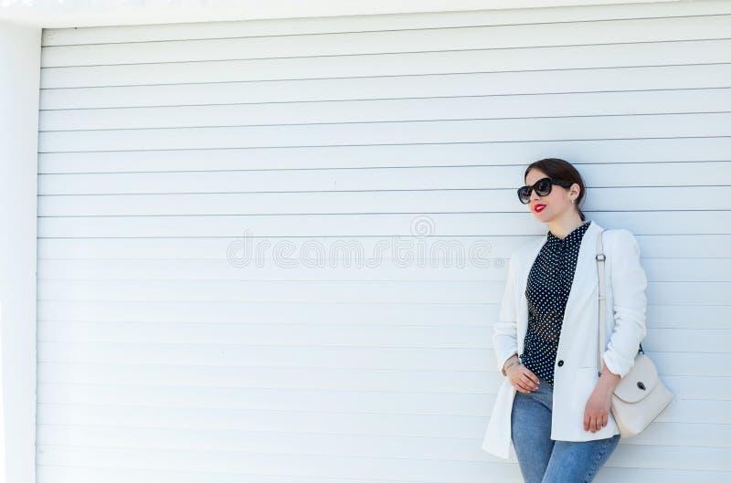 Härlig flicka i det vit omslaget och jeans på vit bakgrund för garagedörrvägg Moderiktig tillfällig modedräktsommar arkivbilder
