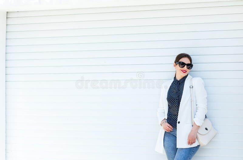 Härlig flicka i det vit omslaget och jeans på vit garageväggbakgrund Moderiktig tillf?llig modedr?kt i sommar royaltyfri fotografi