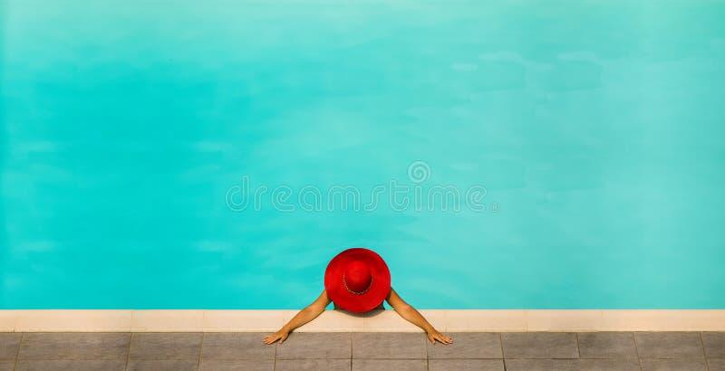 Härlig flicka i en baddräkt och en röd hatt i en pöl för blått vatten arkivfoto