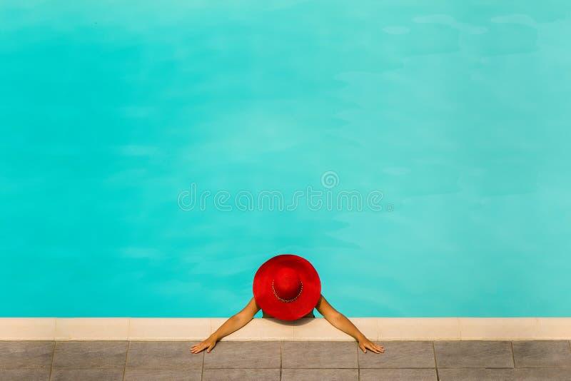 Härlig flicka i en baddräkt och en röd hatt i en pöl för blått vatten arkivbild