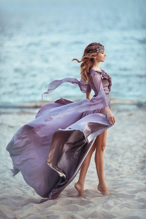 Härlig flicka i en felik purpurfärgad lång klänning på en kust arkivbild