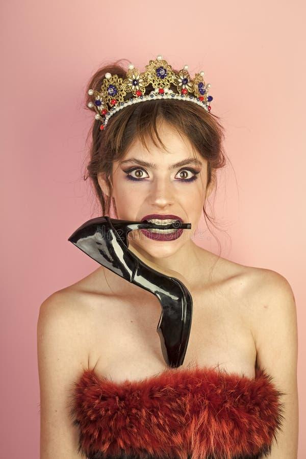 Härlig flicka i en guld- krona på rosa bakgrund med skon i mun royaltyfria bilder