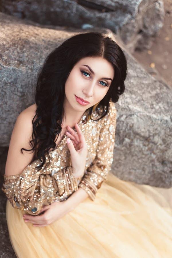 Härlig flicka i en guld, lyxig klänning royaltyfri fotografi