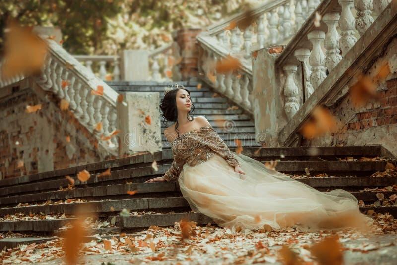Härlig flicka i en guld, lyxig klänning royaltyfria bilder