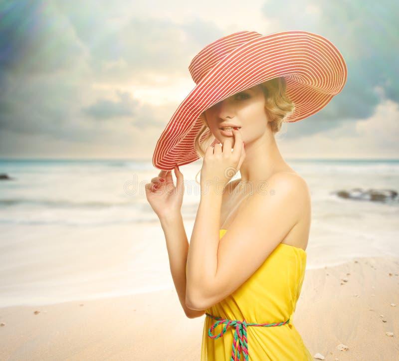 Härlig flicka i en hatt som tycker om solen på stranden. royaltyfria bilder
