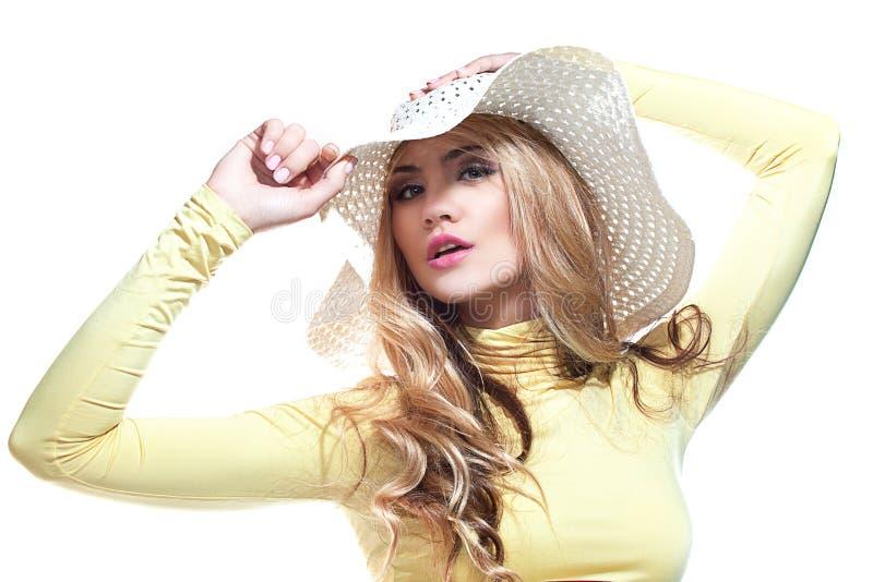 Härlig flicka i en hatt som tycker om solen på stranden royaltyfri bild