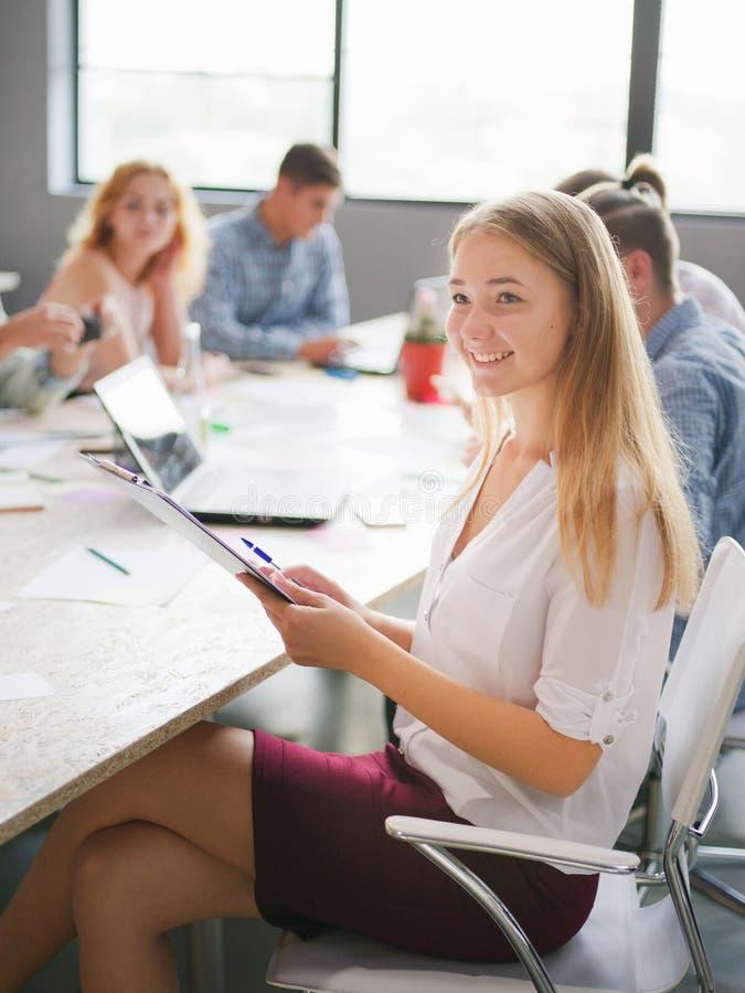 Härlig flicka i en kontorsgrupp människor royaltyfri foto
