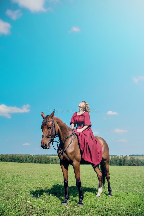 Härlig flicka i en lång röd klänning som rider en brun häst mot en blå himmel fotografering för bildbyråer