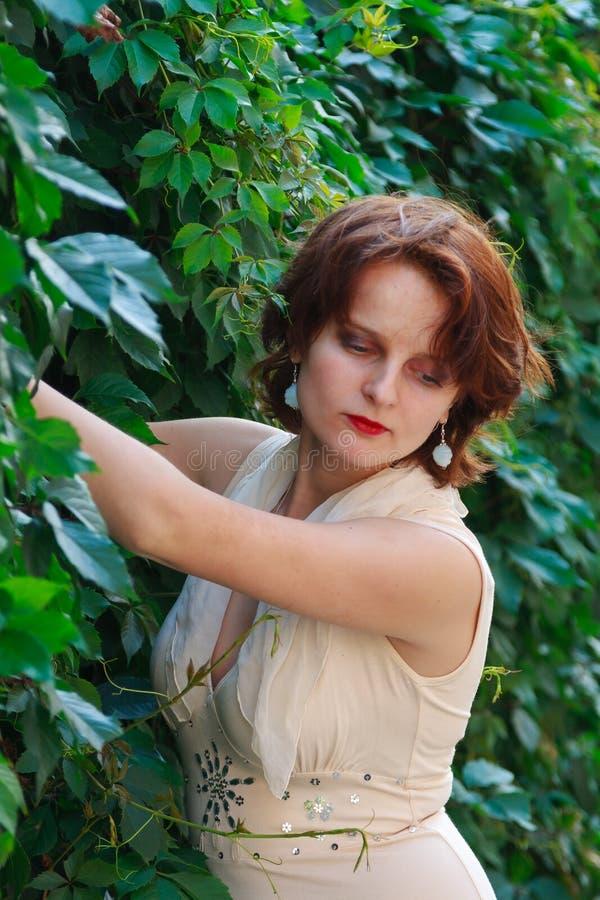 Härlig flicka i en ljus beige klänning i gröna sidor fotografering för bildbyråer