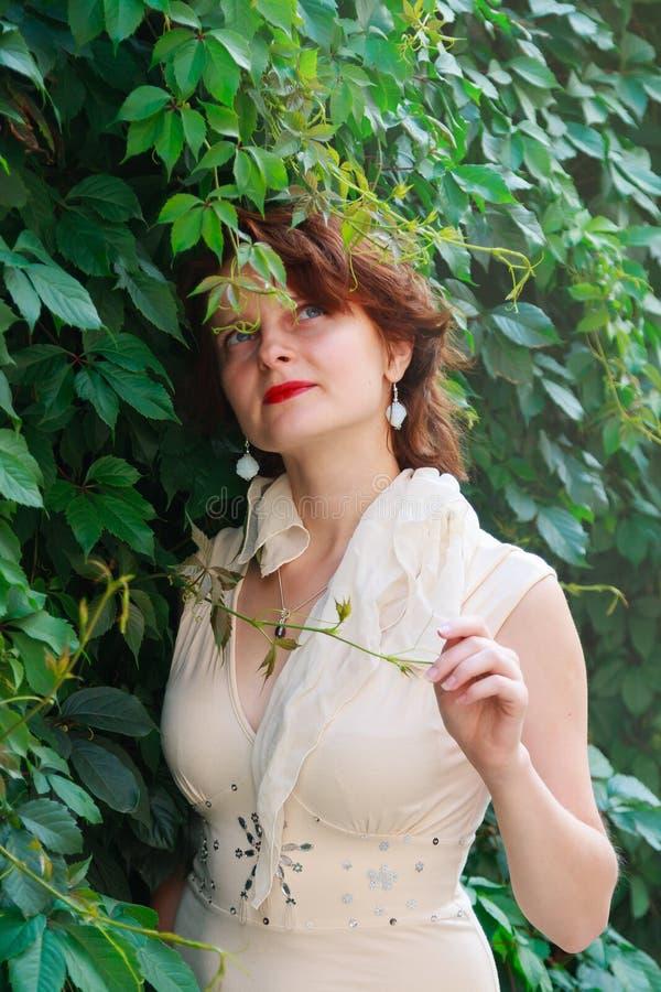 Härlig flicka i en ljus beige klänning i gröna sidor arkivbilder