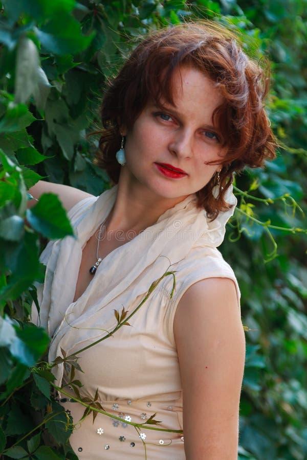 Härlig flicka i en ljus beige klänning i gröna sidor royaltyfria bilder