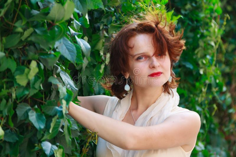 Härlig flicka i en ljus beige klänning i gröna sidor arkivfoton