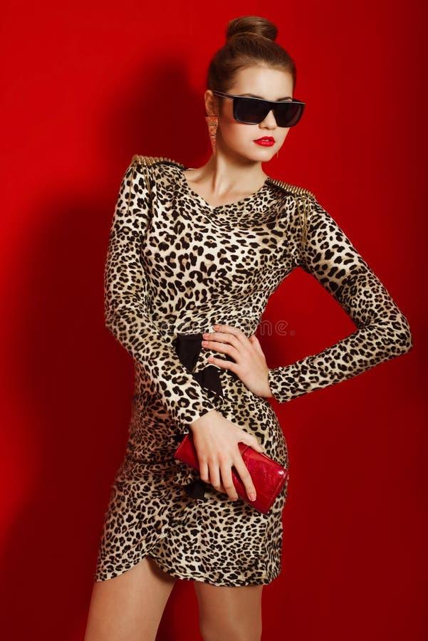 Härlig flicka i en moderiktig klänning och en röd koppling royaltyfri bild