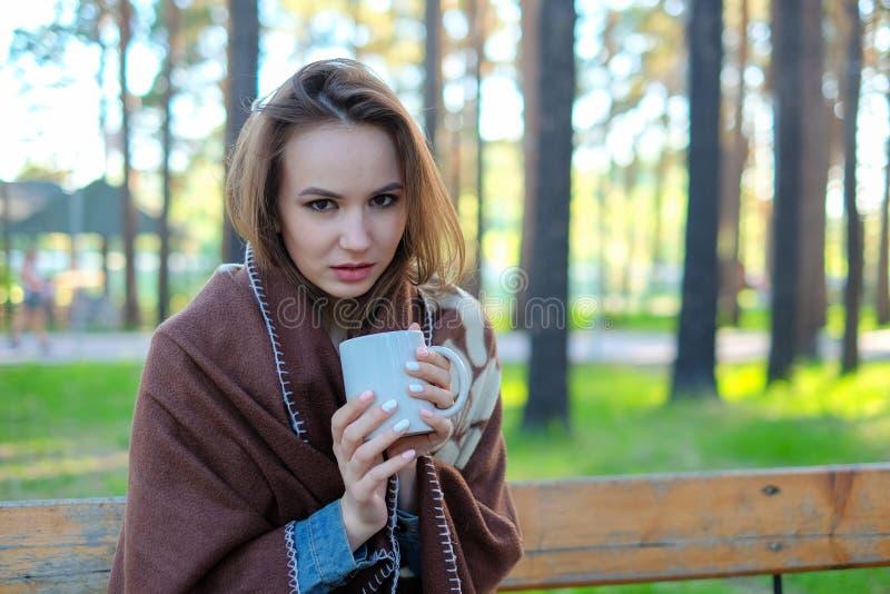 Härlig flicka i en pläd som dricker kaffe i parkera royaltyfri foto