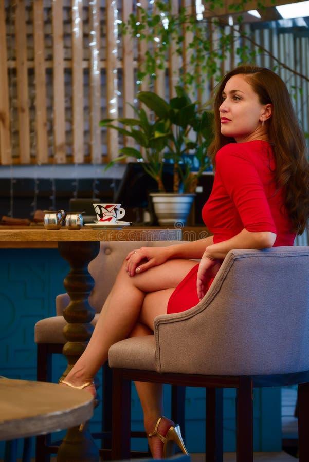 Härlig flicka i en röd stilfull klänning royaltyfri foto