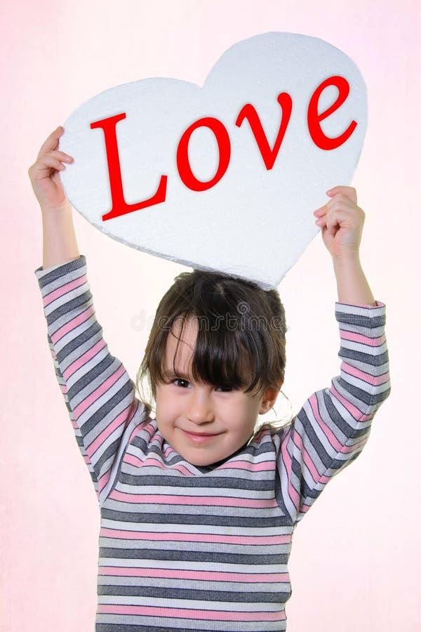 Härlig flicka i en randig blus som ler och rymmer en vit hjärta med inskriftförälskelsen fotografering för bildbyråer