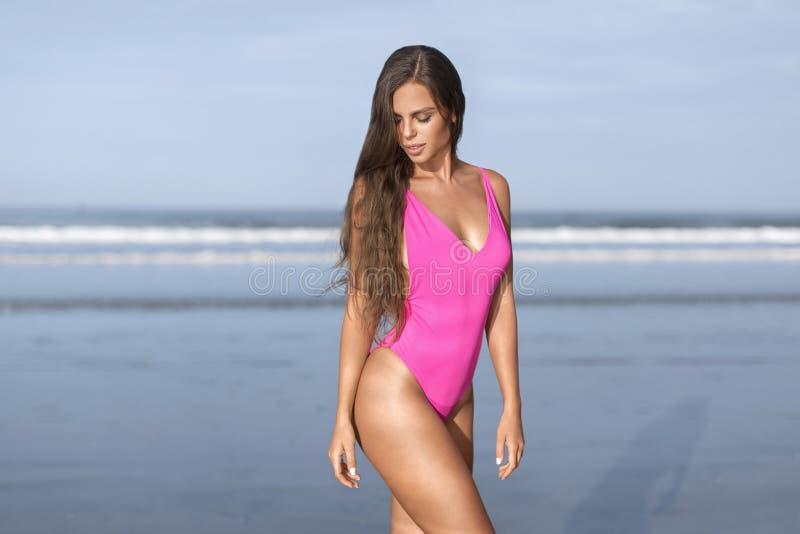 Härlig flicka i en rosa baddräkt på det blåa havet på gryning arkivfoto