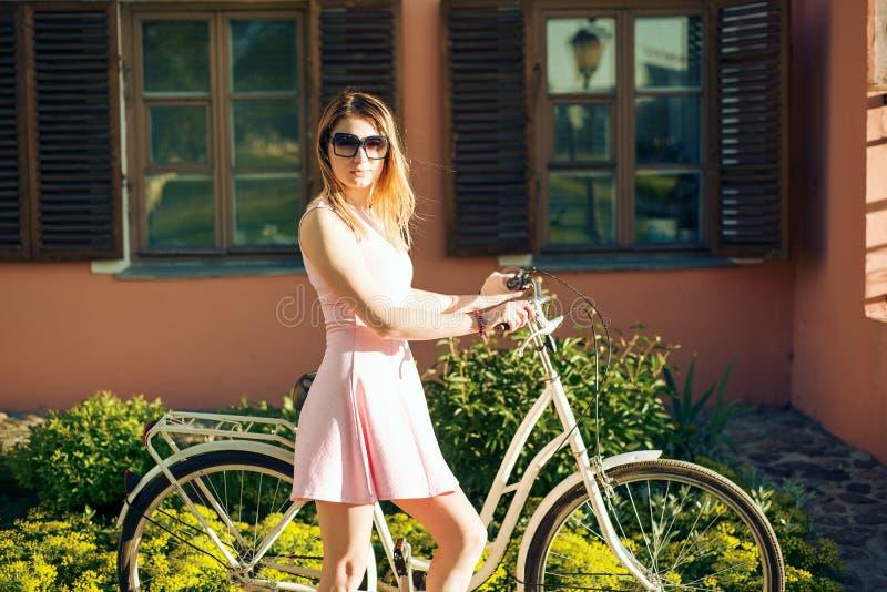 Härlig flicka i en rosa klänning med blommor på en cykel royaltyfria bilder