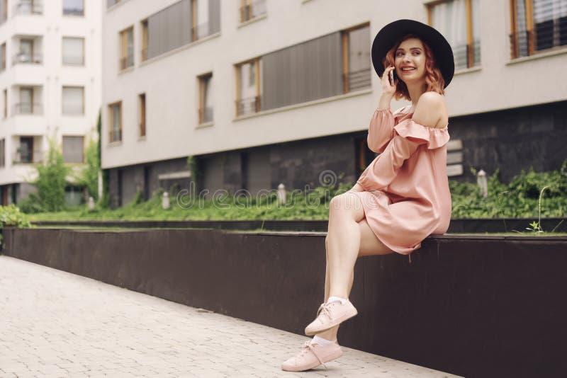 Härlig flicka i en rosa klänning som sitter nära höghus flickatelefonen talar Kvinna med rosa hår i en svart hatt fotografering för bildbyråer