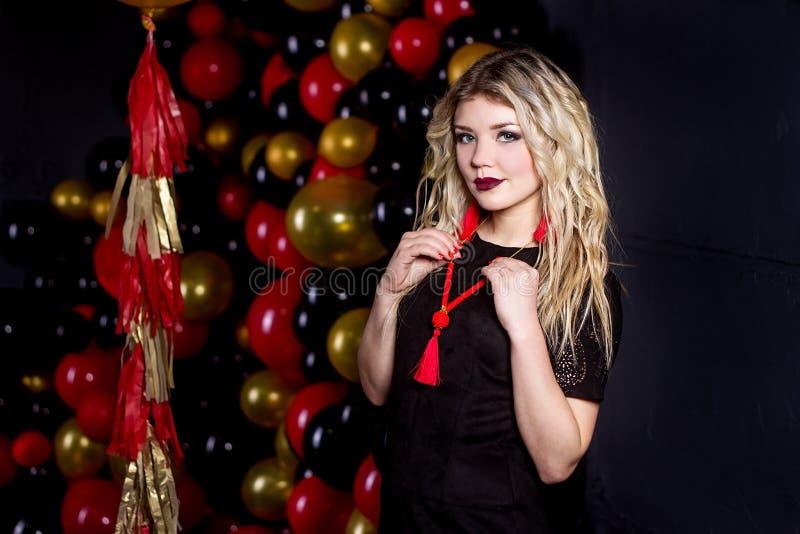 Härlig flicka i en sexig klänning på en studio i en ballonsbakgrund royaltyfri foto