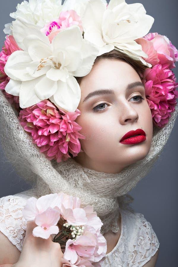 Härlig flicka i en sjalett i den ryska stilen, med stora blommor på hans huvud och röda kanter Härlig le flicka royaltyfri foto