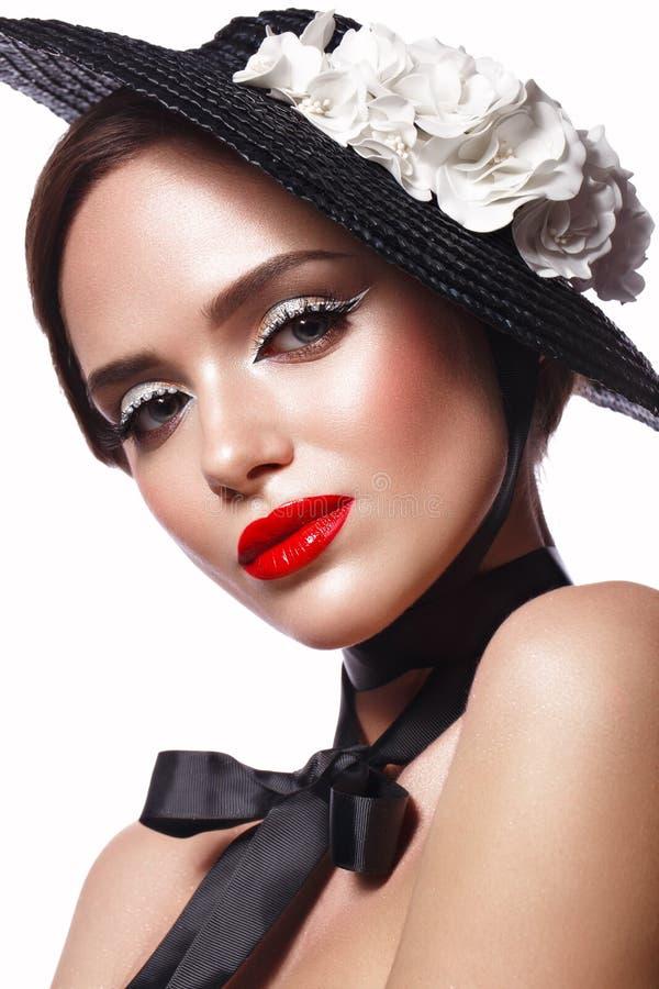 Härlig flicka i en svart hatt med blommor och retro makeup Härlig le flicka arkivfoto