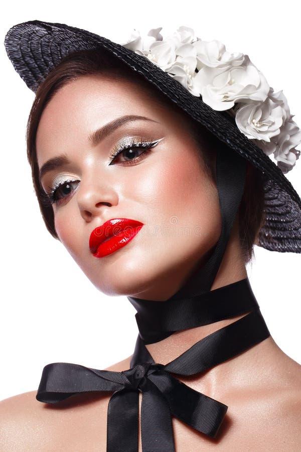 Härlig flicka i en svart hatt med blommor och retro makeup Härlig le flicka arkivfoton