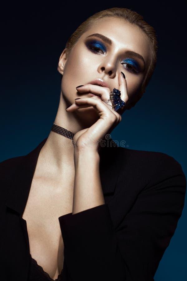 Härlig flicka i en svart klänning, ett rakt hår och en moderiktig makeup Glamourskönhetframsida royaltyfri bild