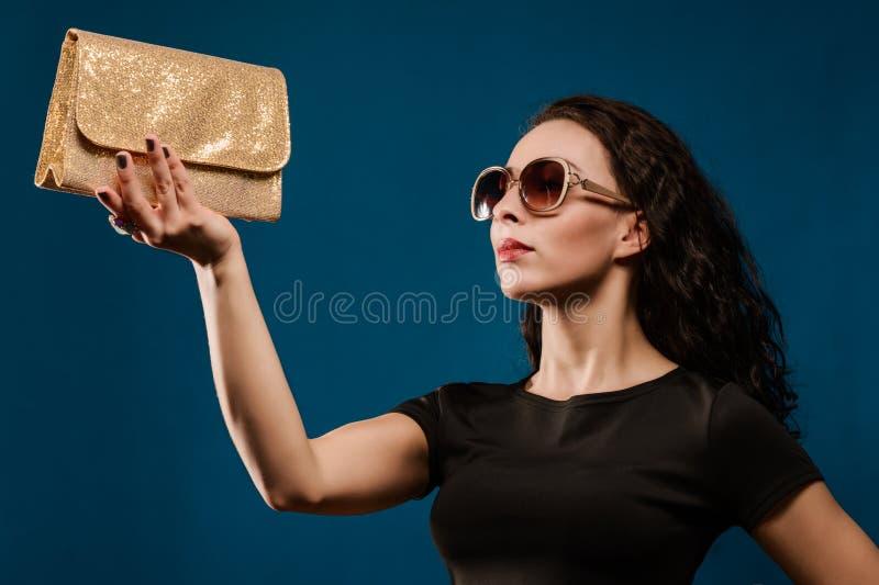 Härlig flicka i en svart klänning med den guld- kopplingen arkivfoton