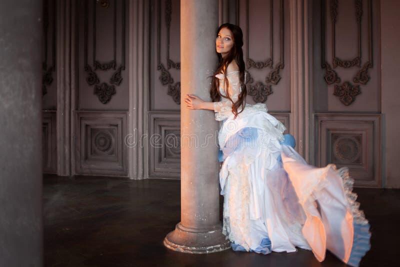 Härlig flicka i en tappningklänning, i dyster inre, gotiskt och saga royaltyfria bilder