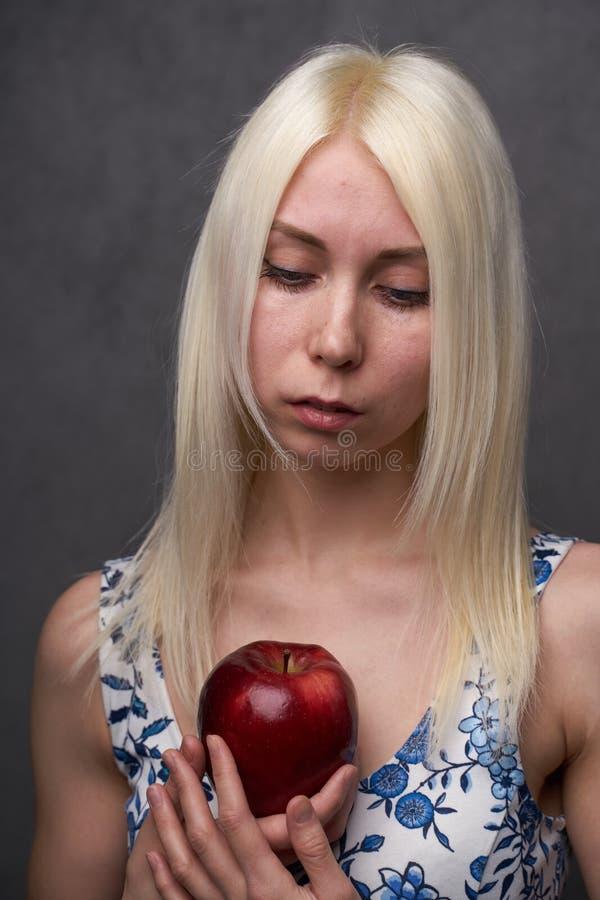 Härlig flicka i en trendig klänning med äpplet arkivfoton