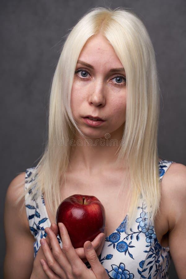 Härlig flicka i en trendig klänning med äpplet fotografering för bildbyråer