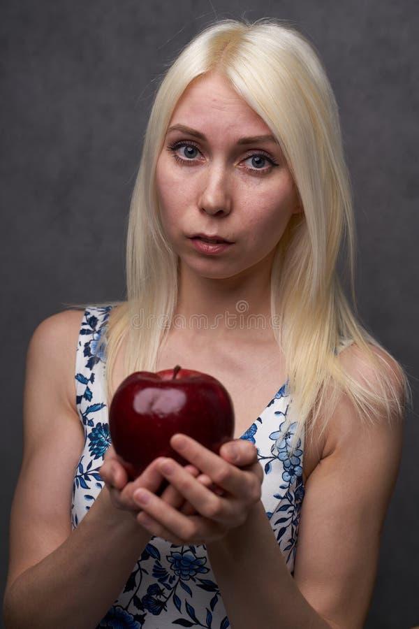Härlig flicka i en trendig klänning med äpplet arkivbild