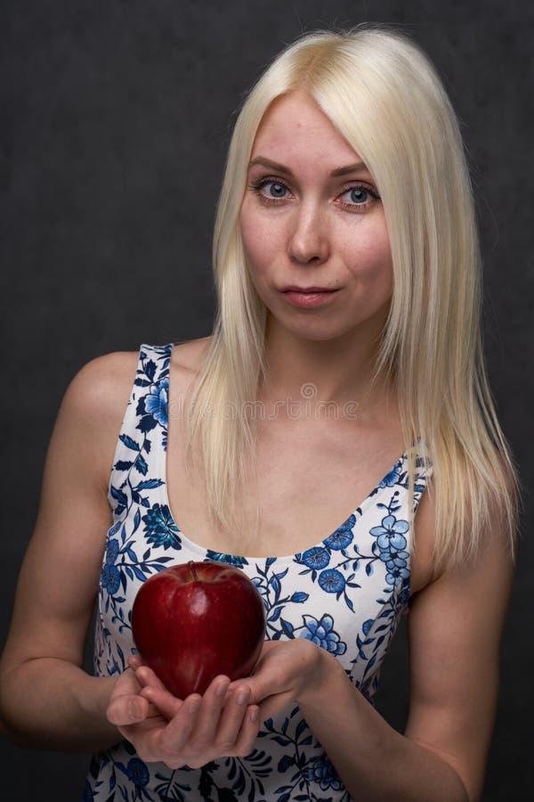 Härlig flicka i en trendig klänning med äpplet royaltyfri fotografi
