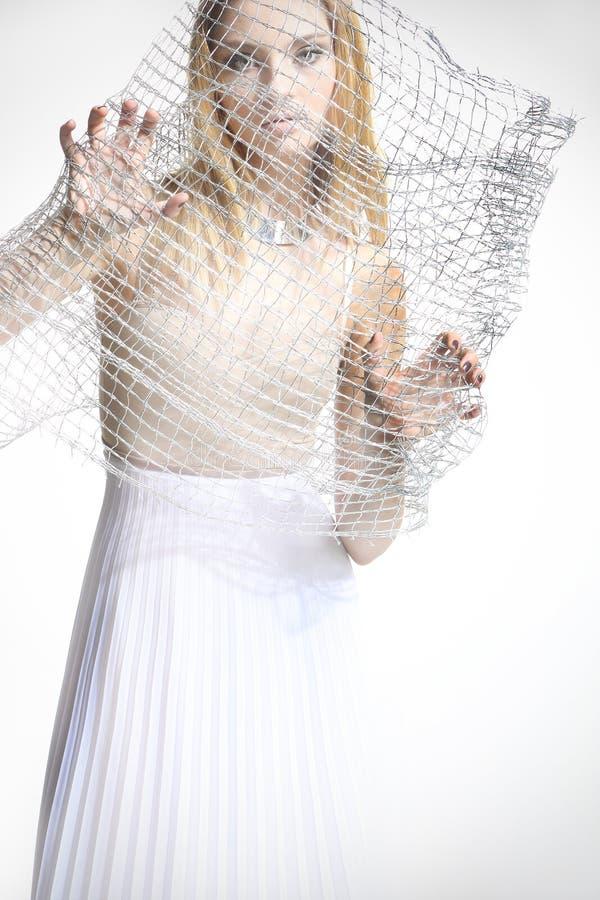 Härlig flicka i en vit klänning som täckas med ett ingrepp arkivbilder
