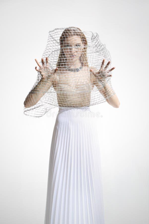 Härlig flicka i en vit klänning som täckas med ett ingrepp fotografering för bildbyråer