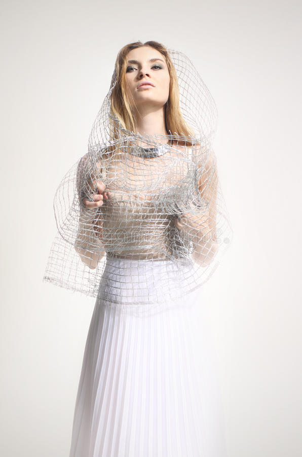 Härlig flicka i en vit klänning som täckas med ett ingrepp royaltyfria foton