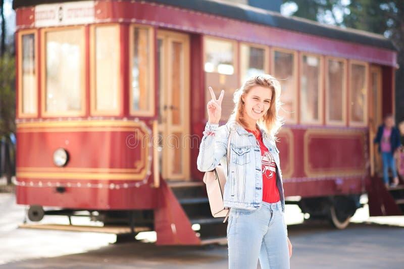 Härlig flicka i ett blått grov bomullstvillomslag och jeans mot en röd spårvagn Kvinnan visar världen med gester i solnedgångsole royaltyfri fotografi