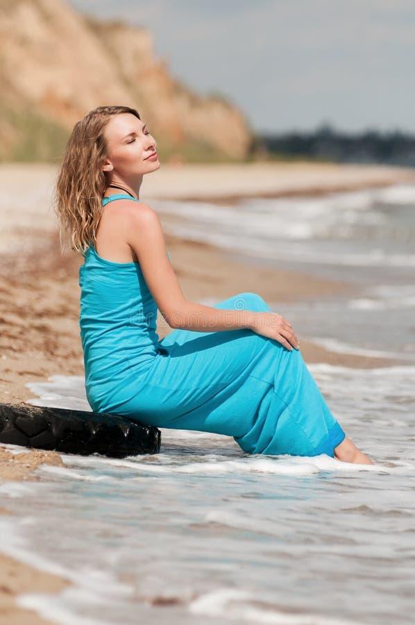 Härlig flicka i ett blått klänningsammanträde på stranden arkivbilder