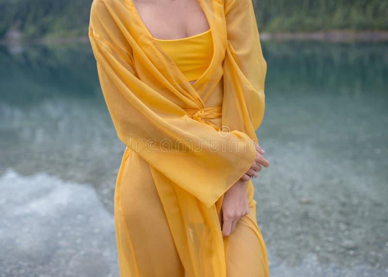 Härlig flicka i ett ljust - gul klänning på en sjö i bergen arkivfoton