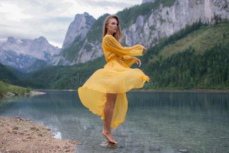 Härlig flicka i ett ljust - gul klänning på en sjö i bergen royaltyfria foton
