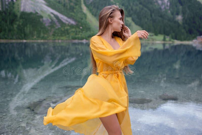 Härlig flicka i ett ljust - gul klänning på en sjö i bergen arkivfoto