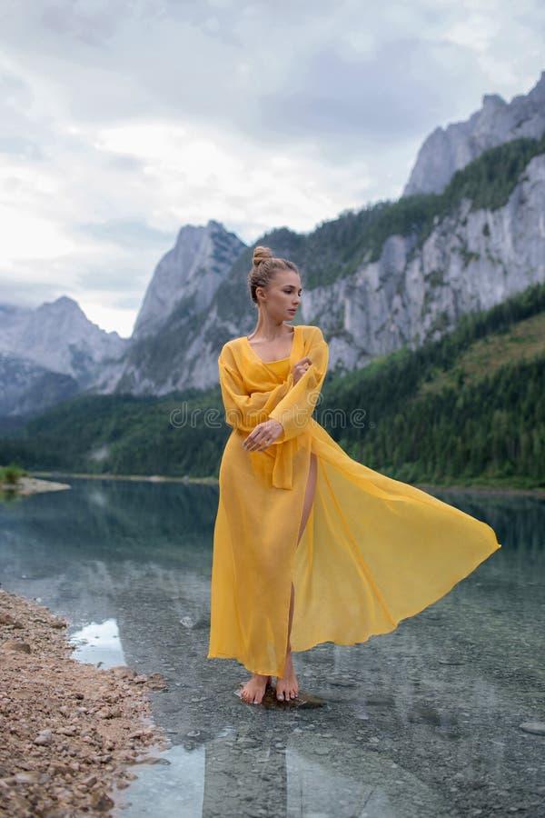 Härlig flicka i ett ljust - gul klänning på en sjö i bergen royaltyfri bild