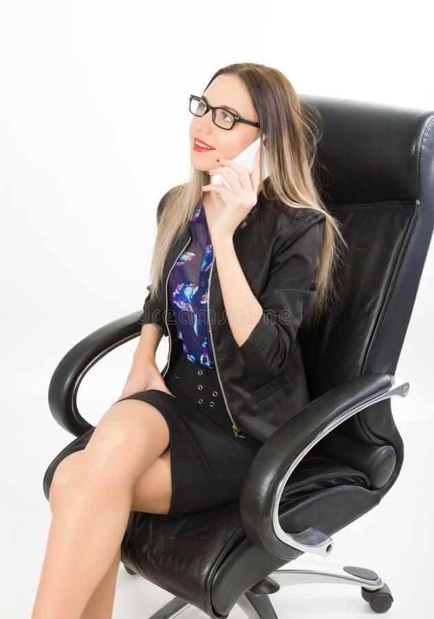 Härlig flicka i ett sammanträde för affärsdräkt i en läderfåtölj royaltyfria bilder